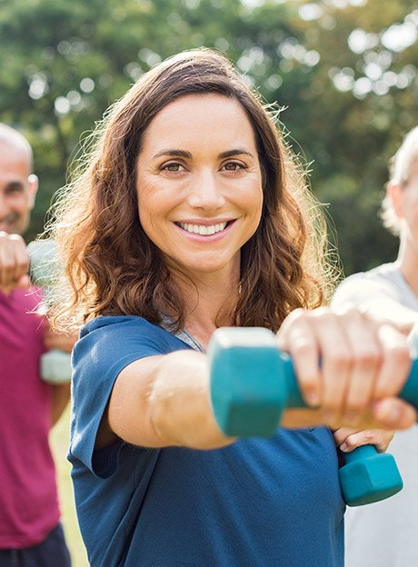 Smiling woman exercising with hand weight