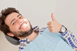 Man smiling with thumbs up in dental chair